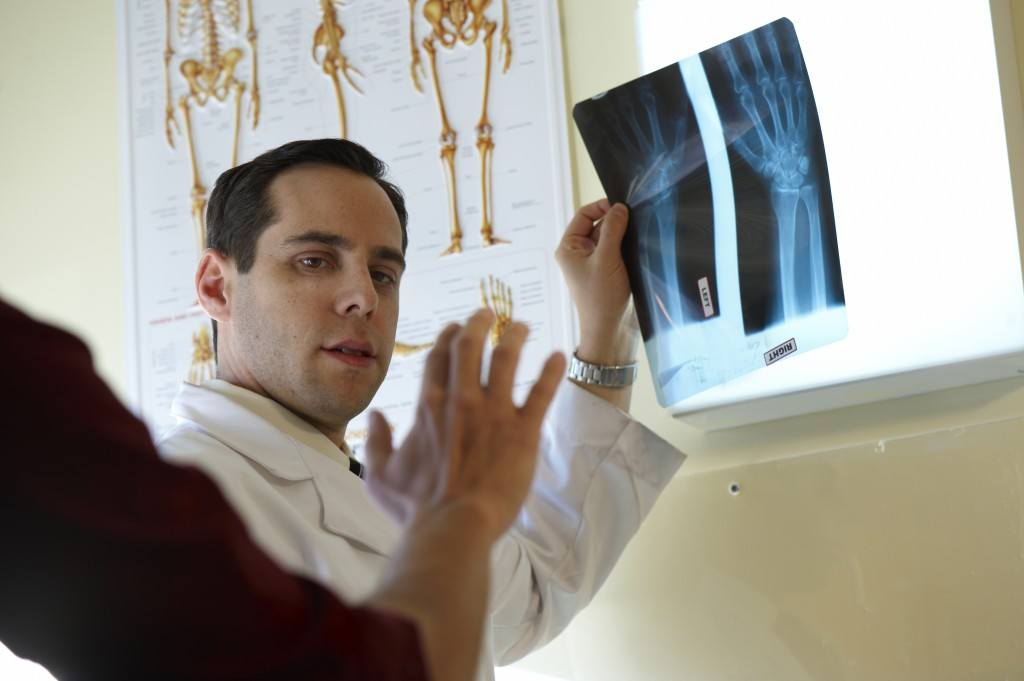 Dr. Edelstein using X-ray of hand to evaluate patient's hand injury